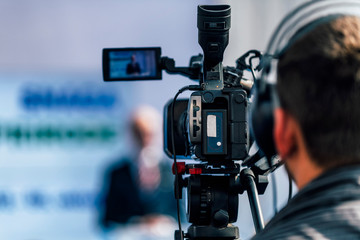 Media Event. Camera Recording Male Speaker On Stage