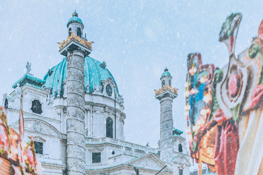 Part of merry-go-round on Vienna Christmas market with St. Charles Church in the background during light snow fall