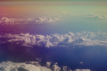 Airplane illuminator view on fluffy cumulus clouds and blue sky. Aerial view background.