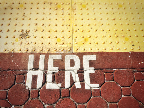 Word HERE painted on to rust colored paving stones.