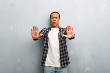 Young african american man with checkered shirt making stop gesture for disappointed with an opinion