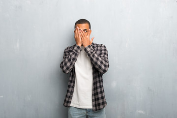 Young african american man with checkered shirt covering eyes by hands and looking through the fingers