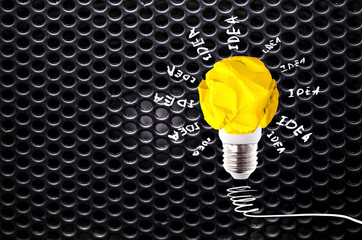Wall Mural - crumpled yellow paper light bulb with inscription idea on dark gray circle mesh pattern