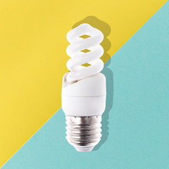 Wall Mural - spiral light bulb on blue yellow  background