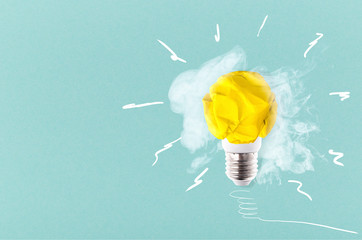 Wall Mural - crumpled yellow paper light bulb on a blue background with smoke, concept idea