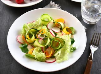 Vegetable salad from zucchini, radish, greens