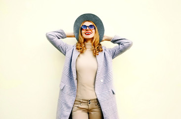 Beautiful happy young smiling woman in pink coat, round hat on wall background
