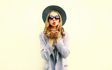 Portrait pretty young woman blowing red lips sends air kiss in round hat on wall background