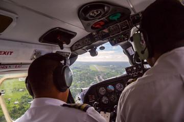 Two pilots landing a small aircraft to Nausori airport airstrip near Suva, Fiji, Melanesia, Oceania. Air travel in Fiji, view from airplane cockpit window. Viti Levu island, South Pacific Ocean