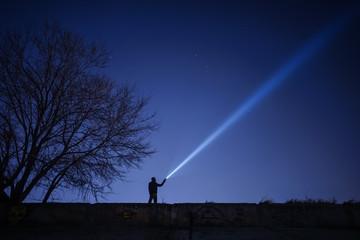 Man pointing flashlight to sky at night.