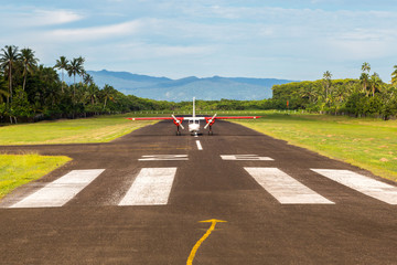 Air travel in Fiji, Melanesia, Oceania. A small propeller airplane just landed to a remote airstrip overgrown with palms, lost in jungle Levuka town, Ovalau island. Viti Levu big island in background