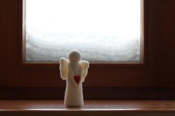 Woolen toy angel standing on a windowsill against a snowy window