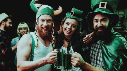 Two Men And Girl In Carnival Hats Drinking Beer.