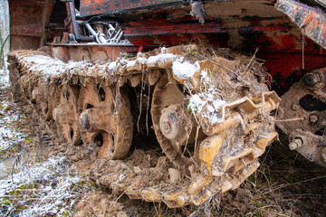 track closeup of Rusty abandoned caterpillar snow tractor on winter surrounding, russia