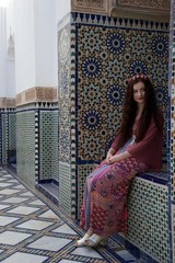 Hippie girl smiling next to beautiful Moroccan tiling