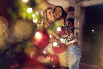 female friends hugging and celebrating Christmas.