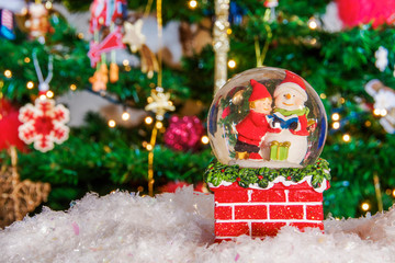 Christmas snow globe ball before blurred background with space for text.Decorating Christmas dome ball with child next to snowman and artificial snow before a lit Christmas tree.