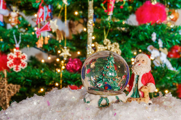 Christmas snow globe ball before blurred background with space for text.Decorating Christmas dome ball with Santa Claus and artificial snow before a lit Christmas tree.