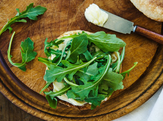 English muffin sandwich with mixed greens being prepared