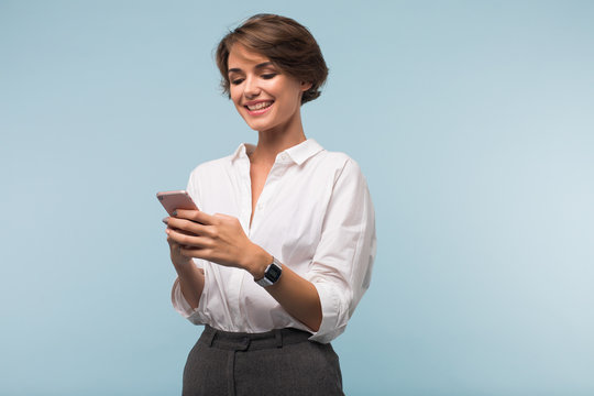 Young pretty smiling woman with dark short hair in white shirt happily using cellphone over blue background isolated