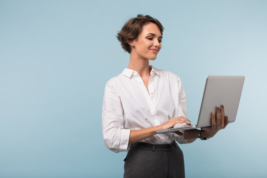 Young smiling businesswoman with dark short hair in white shirt happily working on laptop over blue background isolated
