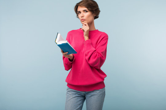 Young pretty pensive woman with dark short hair in pink sweater and jeans  holding little book in hand while thoughtfully looking aside over blue background