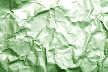 Blurred abstract background of crumpled green paper surface. Cropped shot, horizontal, blurred, top view.