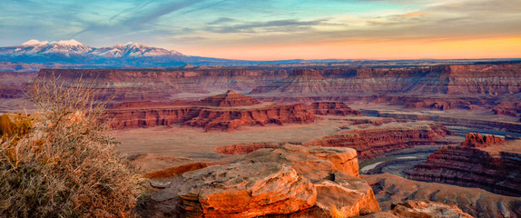 Sunset over Dead Horse Point Southern Utah with snow covered mountains in distance