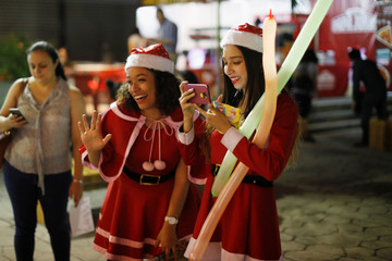 """Assistants of Icelander Einar Sveinsson, dressed as Santa Claus, try to get the attention of a child as he poses for a picture during the """"Villa Navidad"""" Festival in San Salvador, El Salvador"""