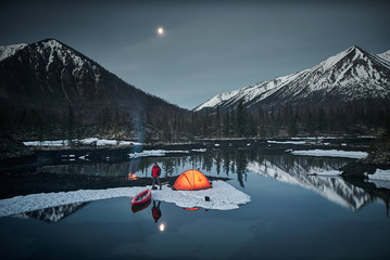 View of camp life in a mountain terrain in spring time. Lake shore with canoe