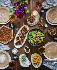 Modern spring tablescape with Lamb, spring salad, golden beets, mixed drinks, and Pecan pie