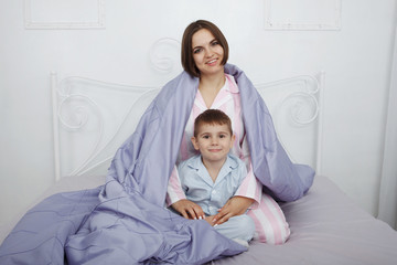 Young beautiful woman mother sitting under a blanket with children in bed with blue linens.