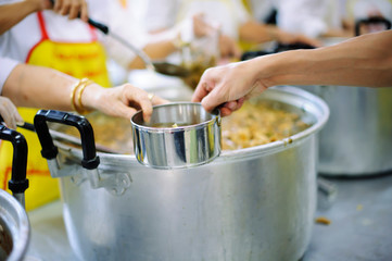 Hands of the poor are waiting for food donations to alleviate hunger : concept of feeding