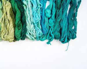 Rainbow color threads for embroidery on a white background.