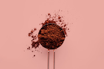Rose gold measuring cup of cocoa powder on a pink background, healthy food concept