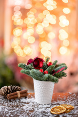 Christmas arrangement with Norwegian pine Nobilis and decorated with Christmas decor in a coffee Cup. Garland bokeh on background. Christmas love. Dark wooden table sprinkled with snow