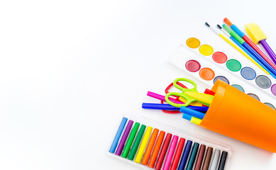 Pencils and felt-tip pens in a plastic cup, paints and pastel crayons on a white background