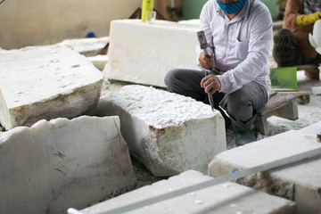 senior sculptor hands working on his marble sculpture in his workshop
