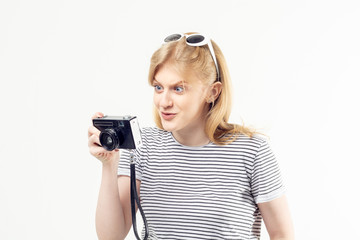 Pretty blonde teenage girl in striped t-shirt looking at the vintage camera in her hands with curious and surprised expression on her face