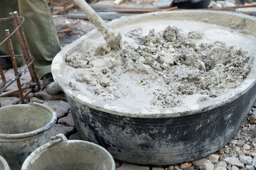 Worker mixing concrete cement mortar