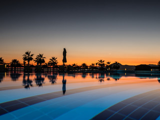 Sunset with silhuettes palm and reflection in swimming pool