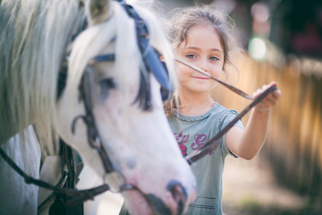 Portrait of a little girl with a pony