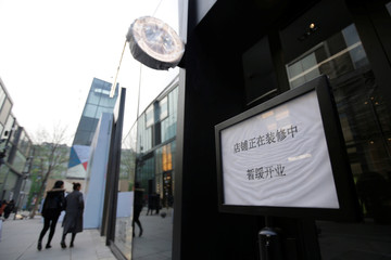 "A sign reading ""delayed to open for construction"" is placed in front of a Canada Goose store in Beijing's Sanlitun area"