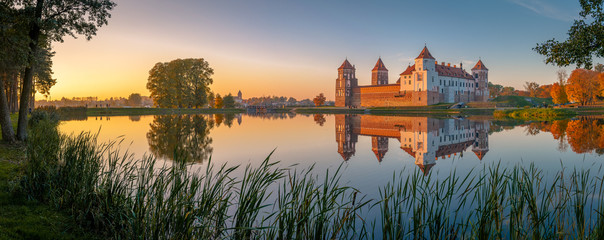 Stores photo Bleu jean Mir castle in the sunsetlight. Belarus. Panorama