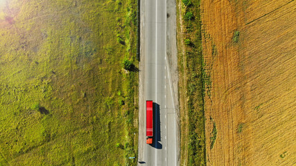 Aerial. Red truck on a road between fields.