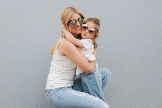 Beautiful mothe with her daughter. Blond hair female. Gray background. Best friends
