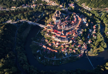 View from above on medieval city Loket with gothic Castle Loket, Burg Elbogen, surrounded by river and green hills,massive fortification illuminated by setting sun.Close to Karlovy vary,Czech republic