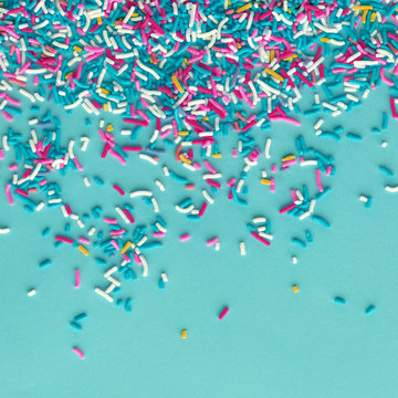 Colorful sprinkles on a blue background, top view with copy space