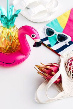 Summer vibes concept with colorful travel fashion items, sunglasses, scarf, pink dragon fruit, flamingo inflatable drink holder, pineapple straw tumbler bottle, net bag and sandal on a white backgroun