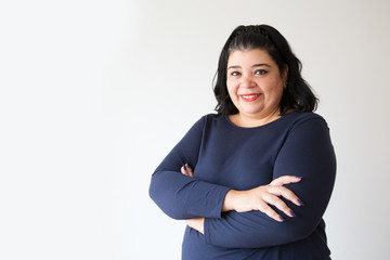 Successful overweight Hispanic woman posing with crossed arms. Smiling adult plus size woman looking at camera. Isolated on white. Success concept